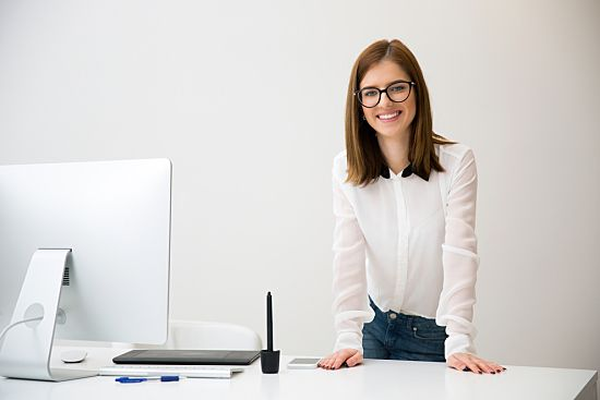Smiling woman standing at her desk