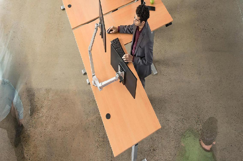 An  person using dual monitors on an L-shaped standing desk