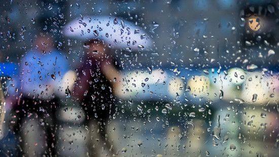 A women walking outside in a rainy day with an umbrella