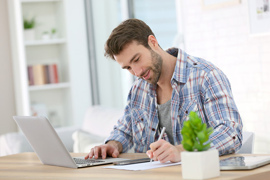 Businessman at home working on laptop
