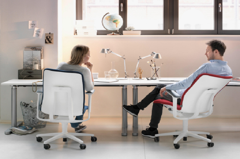 Two workers sitting on the ergonomic desk chairs