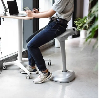 Person using a chair for standing desk