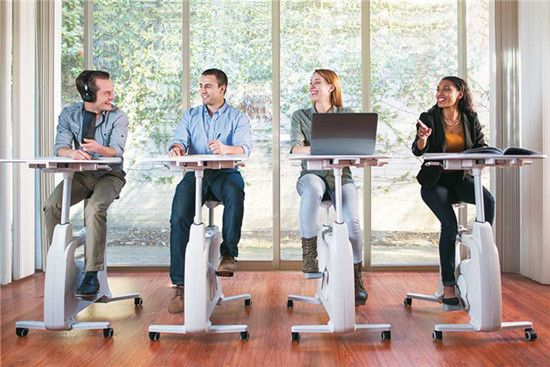 Four workers are using desk bikes while working