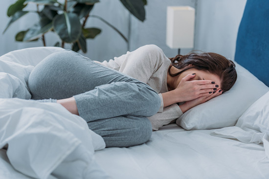 Depressed woman lying in bed, crying and covering her face with both hands