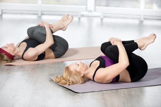 Two women performing knee-to-chest stretch