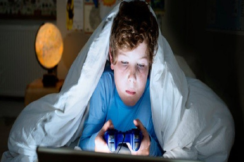 A kid who plays video games under the sheet