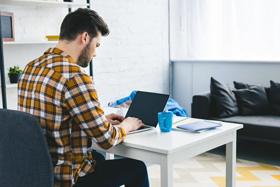 Man working by table with laptop in light office