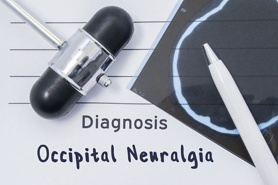 A massager and a piece of paper shows Occipital Neuralgia