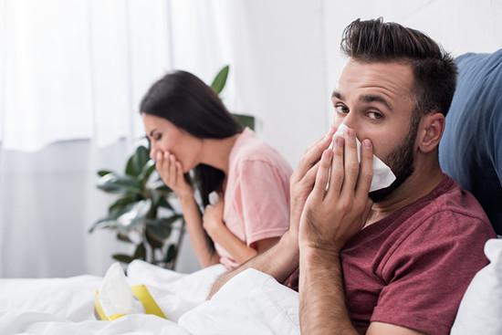 Sick young couple sneeze into a tissue while sitting on the bed