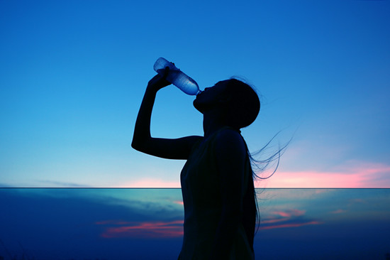 Silhouette of woman hydrating and refreshing at sunset