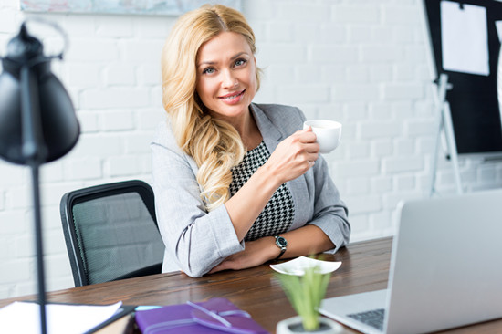 Smiling businesswoman holding a coffee cup in the office looking at the camera