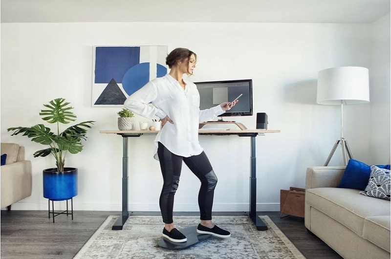 exercisng on a standing desk balance board