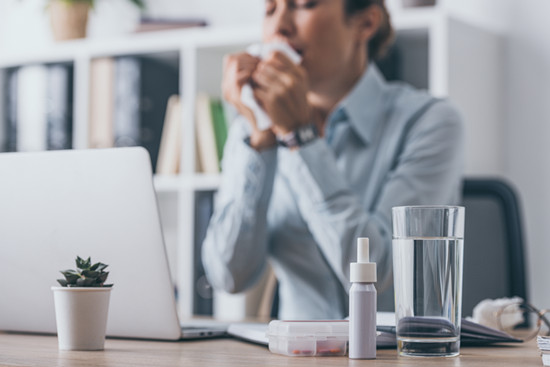 Standing table vague drugs sneezing businesswoman sitting in the background