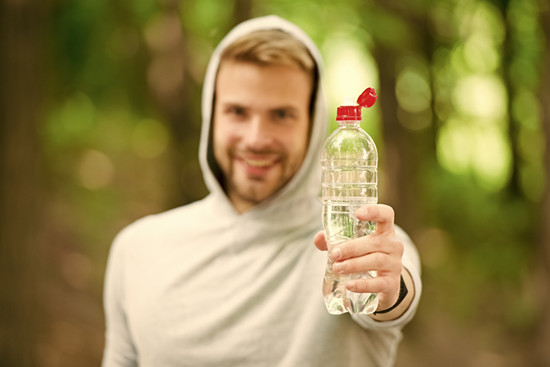 Stay hydrated. Man athletic sportsman hold bottle water