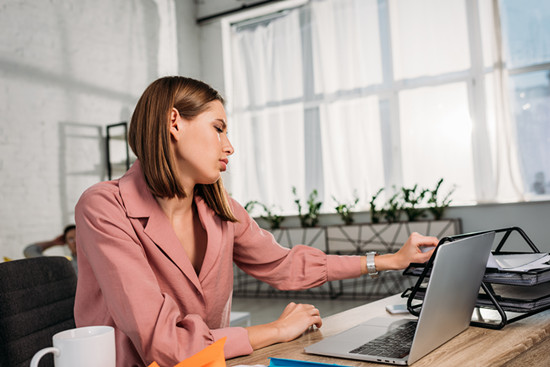 Tired attractive woman sitting at desk near laptop at home
