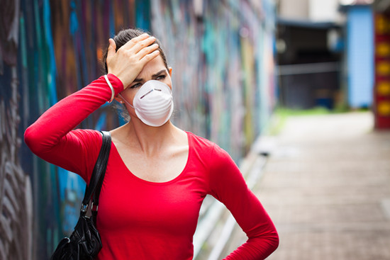 Woman with headache wearing a face mask