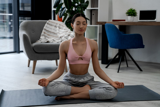 Young charming and attractive female athlete smiling while practicing yoga