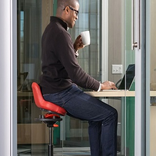 A person sitting on an ergonomic chair for standing desk