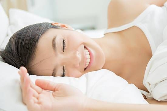 Woman waking up on her side with her head on a pillow