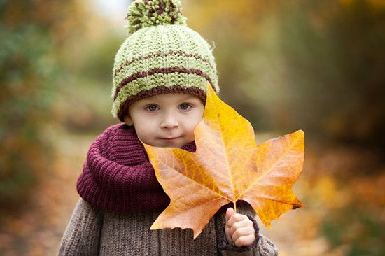 A kid is holding a leaf in Autumn