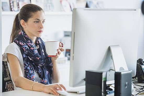 A woman drinking coffee at her computer