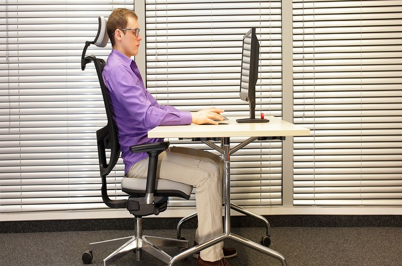 A tall person using the proper ergonomic chair