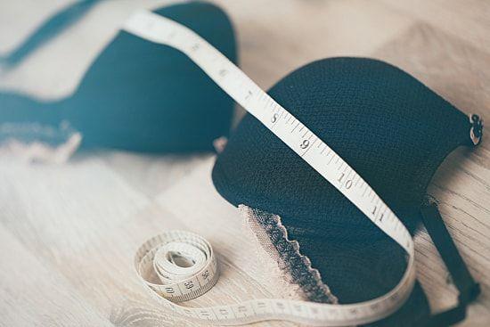 A black bra with a fabric measuring tape.