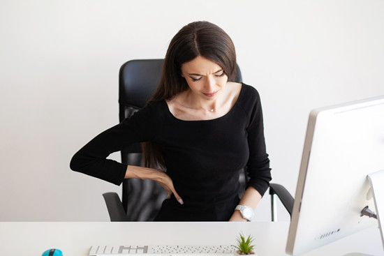 Woman suffering from back pain while working with laptop at office