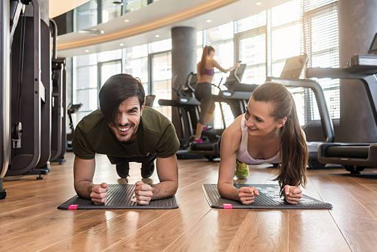 A young couple does a forearm plank at the gym