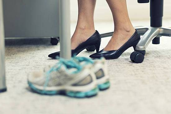 Woman at desk with workout shoes.