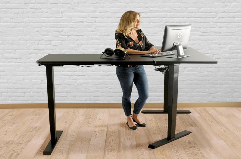 A worker typing on a corner sit stand desk
