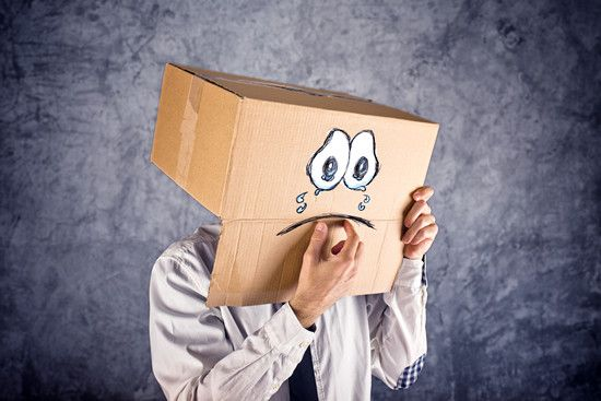 A staff is crying behind a box