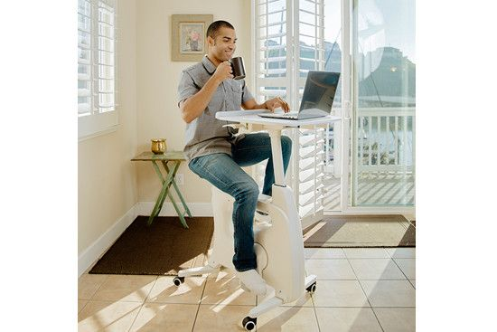 A man is using flexispot desk bike while working