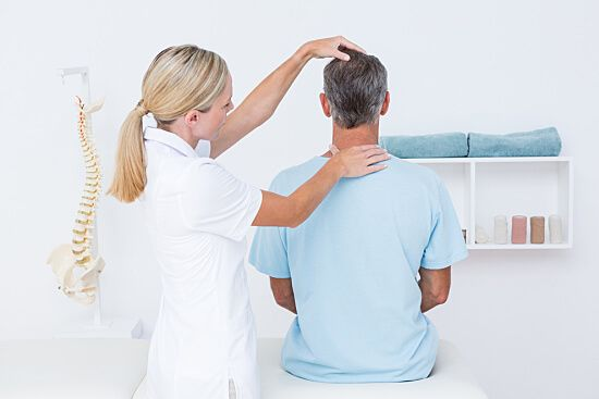 Chiropractor adjusts male patient's neck