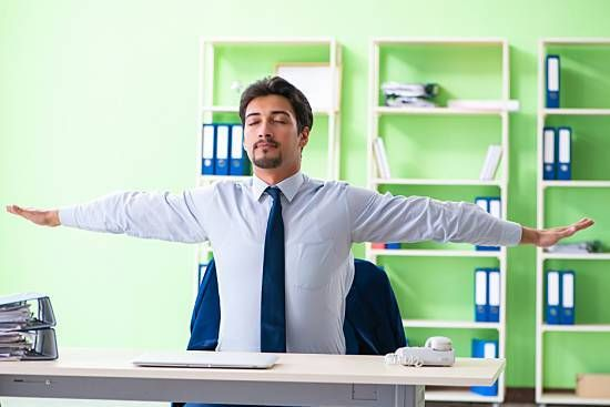 Man exercising in his chair at his desk.