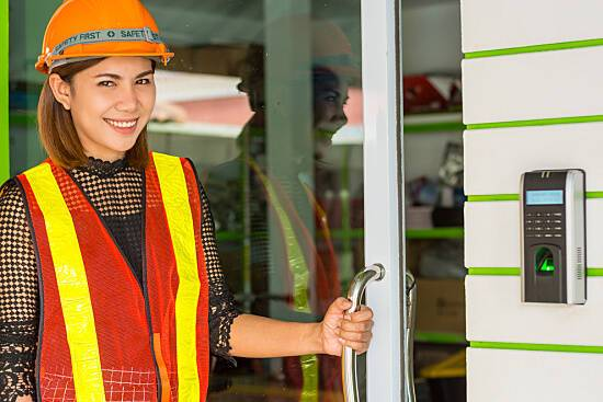 Female employee wears hard hat and vest for workplace safety
