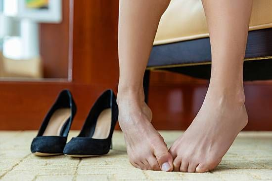 A woman curls her toes in embarrassment after taking off her high heels.