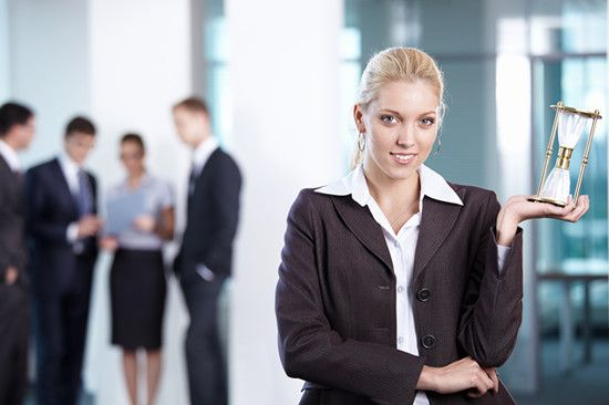 A female employee is holding an hourglass
