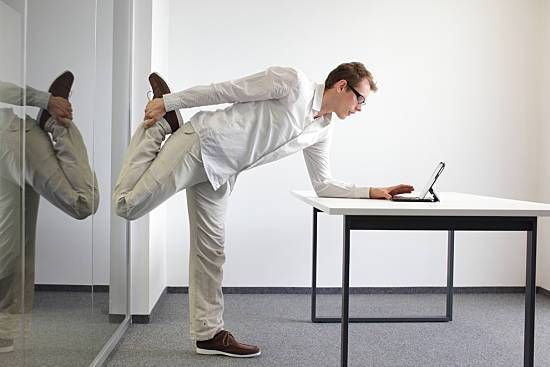 A young man stretching at his desk