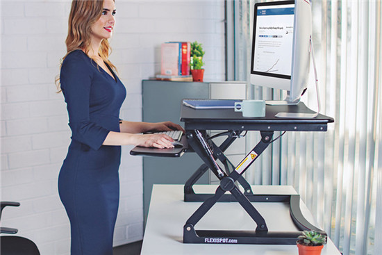 A woman is working with her standing desk converter