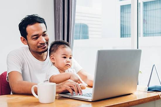 Father with son on his lap working on computer near window