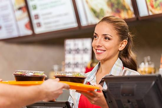 A woman prepares healthy food at a fast food restaurant