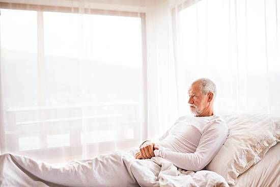 Man in white shirt laying in an adjustable bed