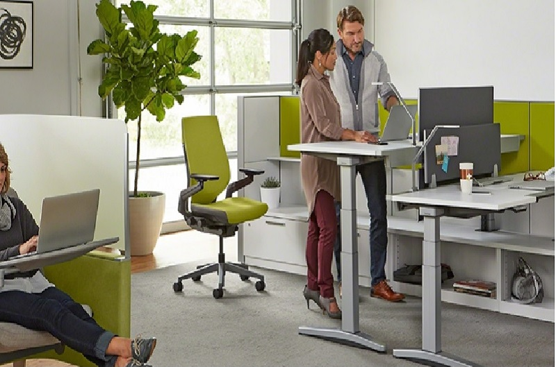 Two people conversing on a standing desk