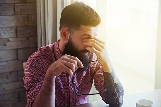 A stressed employee taking a moment to compose himself while dealing with depres