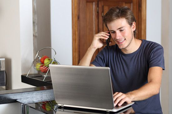 A teen entrepreneur is contacting his client via ceilphone from home