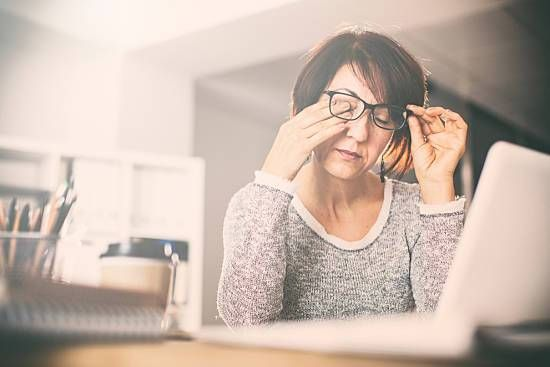 Woman rubs her eyes while sitting at her desk