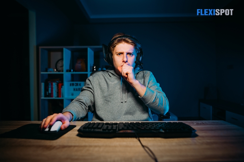 Gamers wearing headsets sit at the table at home in the evening and play online games on computers and streaming media. Games at night in your spare time. The game is like work.