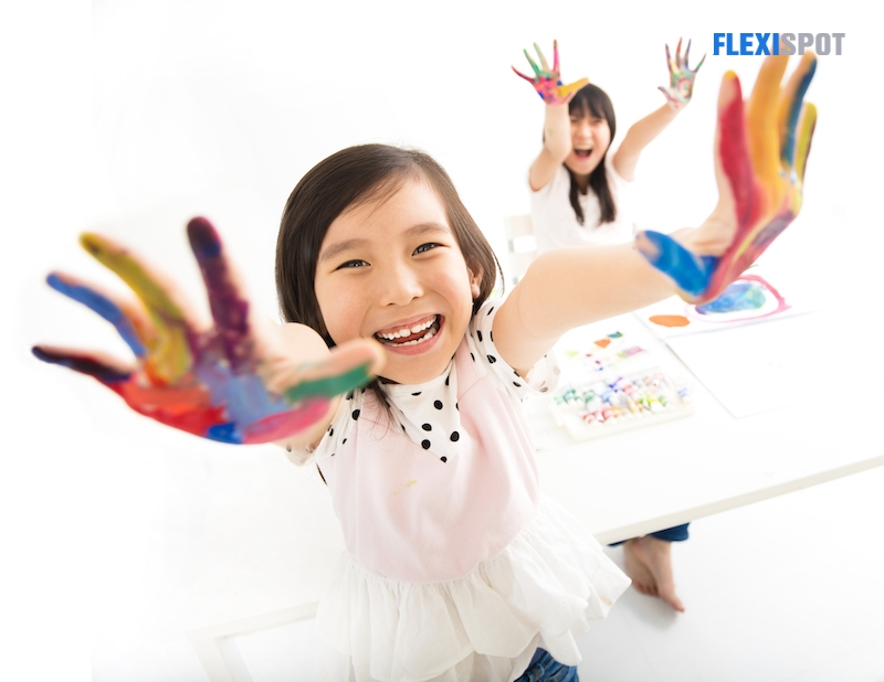 Happy little girl with hands in the paint