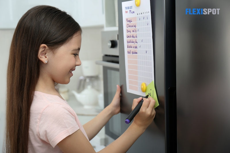 Little girl drawing funny face on note near to do list in kitchen